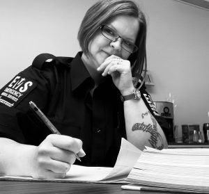 Black and white image of a paramedic seated at a table, holding a pen, textbook open and ready to study